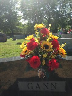 Silk cemetery vase using red roses, yellow sunflowers, yellow forsythia with red ribbon. May 2016
