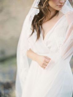 A lovely bride wrapped in long veil @myweddingdotcom