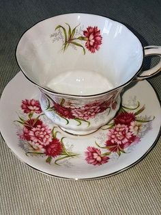 Paragon England white tea cup and saucer, Flower Festival series K Made in the 60s Cup: 3 tall Saucer: 5 1/2 diameter The rims, base, and handle are gilt. Very good condition, no chips, no hairlines, no chips. Rims are unharmed. Paragon was established in 1897 under the name Star China. It started using Paragon as a trade name around 1903 and in 1919 the company name was changed to Paragon China Company Ltd. Known initially for its tea and breakfast fine bone porcelain it expanded in...