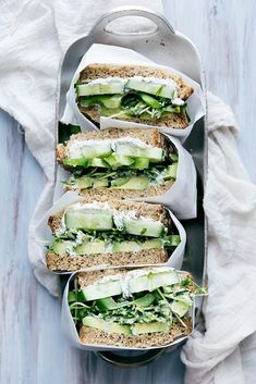 A green sandwich bursting at the seams with herbed goat cheese, avocado, cucumber, alfalfa sprouts, and more.