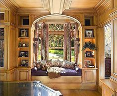 Shouldn't all new homes have a library feature like this one, with a cozy window seat? Beneath leaded glass windows, too, that's a nice touch!
