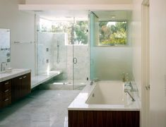 Modern bathroom featuring a glass shower cabin and a stylish under-mount tub