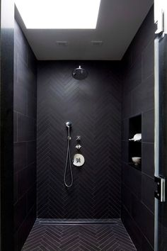 HGTV presents a modern master bathroom shower detail with dramatic black herringbone patterned wall and floor, modern chrome fixtures and shower drain, and skylight.