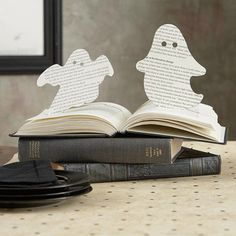 Make a spooky centerpiece from a stack of old books and some pop-up ghostly shapes. To make this project, cut two basic ghost shapes from pages in the middle of a book, leaving the bottoms attached to their pages. Hold up each ghost with a touch of tape. To complete this haunting centerpiece, use a hole punch or marker to make eyes for each ghost.