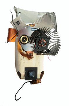 » der Performer «  Bricolage 2014, 20 x 30 x 10cm   Material: Kühlungsrad eines Verstärkers, Akku von meinem ersten Siemens-Mobiltelefon, Blechumhüllung vom ersten CD-Laufwerk, Innerrein aus Apple-Laptop's G3 und älter und aus diverse Apple Macintosh Computer 1995-2009  Medium: Sperrholz-Verpackung eines Biobrotes