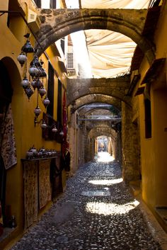 Cobblestone street, arches, lanterns and bright sunlight | Rodhos, Aegean, Greece