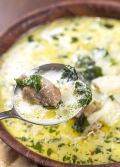 white soup with sausage and kale in brown bowl
