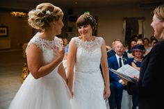 close up of brides laughing at each other whilst speaking vows with registrar laughing