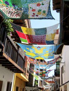 En Valverde de la Vera (España) sus vecinos tienden parasoles que visten las calles de colores. Están tejidos a crochet por ellos mismos usando plástico cortado en tiras, sobre todo proveniente de bolsas.