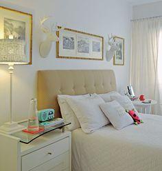 Este quarto clean tem cabeceira da cama em botonê. Para dar um ar mais descontraído, cabeças de alce junto a quadros