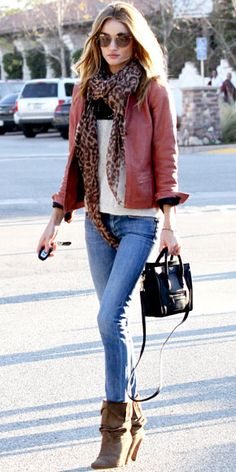 Maroon leather jacket, white shirt, leopard scarf, denim jeans, brown shoes, black bag.