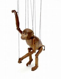 Monkey marionette -  This monkey puppet is called a marionette because it is operated from above, by strings attached to a control bar.    It was carved by Arthur Wilkinson, inspired by the toy Italian puppets he had seen in 1914. He started his career as a professional puppeteer by touring his puppets through England in a caravan, performing with his brother Walter (who later concentrated on the glove puppetry revival).