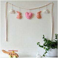 The Needle&I garlands add a whimsical, quirky touch to any child's room. Hang them from the bedroom door, the cot or directly onto the wall itself.The cloud, bunny and heart characters are hand-cut from 100% boiled wool, hand-dyed in peach and pink. The garland is hand-stitched using 100% cotton thread. Each garland features two clouds, two bunnies and one heart with the largest in the centre (approx 100mm wide) and the smallest at the extremes (approx 65mm wide). Button detailing fixes the…