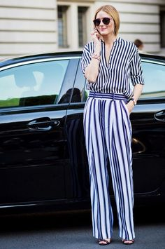 Olivia Palermo wears a striped button-down blouse, striped trousers, sandals, and Dior sunglasses