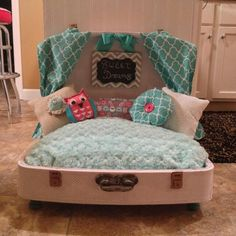 This is a beautiful bed! We have worked very hard to make the cutest, most comfortable, and one of a kind dog bed out there! We spent much time recovering a vintage suitcase with playful pink polka dots inside and out. The bed is made from an ultraplush aqua rosette fabric that your pet is sure to love! The back wall of the bed has fashionably designed aqua curtains and a grey chevron chalkboard sign that you can write on! You can also shop on our etsy shop. www.etsy.com/shop/lateedawgs