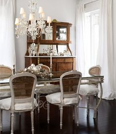 french dining room. love! love the lightness with the tall windows, long flowing curtains, dainty chairs, cupboard, dark wood floor against light walls and furniture.