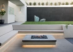 A clean, modern fire pit is flanked by a built-in bench topped with custom cushi. A clean, modern fire pit is flanked by a built-in bench topped with custom cushions that blend into the calm, neutral co. Modern Landscape Design, Modern Landscaping, Backyard Landscaping, Landscaping Ideas, Backyard Ideas, Fence Ideas, Modern Backyard Design, Garden Ideas, Landscape Edging