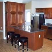 Kitchen with Seneca Ridge cherry paprika cabinets and laminate floor by Rochester Homes | www.rochesterhomesinc.com