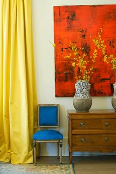 The yellow curtain, red painting and blue chair are perfectly put together, rather than looking like a spilled Crayola box.
