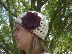 """Ready to ship Hand Crocheted Womens Hat With by WillowPrairie, $24.00 This hat will keep you warm on the cooler days of winter. It is a creamy white with a plum stripe around the bottom and a purple flower. It will make any outfit pop. The wool in this hat is not rough it is wool blend and is pretty soft.  Ready to ship.  Size: adult or teen (21"""" with stretch) Color: White with Plum Fiber: Wool blend  Machine wash and dry!"""