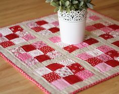 I am excited to be a part of Melissa's Simply Charmed Blog Hop today.  In thinking about what I would like to make with a Charm Pack, I decided to replicate this little mini-quilt/table-topper that I made last fall. I loved having a little zing of color on my normally 'blah' boring kitchen table. Thanks to the generosity of the Fat Quarter Shop I was able to make a festive Valentines mini to festoon my kitchen table for February. (Try saying that 5 times fast.) And today I'll share ...