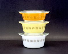 This full set of three vintage Pyrex Bake, Serve and Store Cinderella casseroles in the Town and Country pattern have Hex stars around them and each one comes with a lid. They are a fantastic way to add to your growing Pyrex collection. These unique bowls are oven safe for cooking, but also double as a lovely serving dish, and a fun storage option. The large one is white, the medium is yellow, the small one is orange, and they were made 1963 in the US. There is some minor wear from age, but…