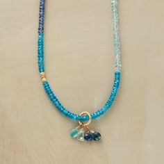 "BLUE BEAUTY NECKLACE�--�Glittery 14kt goldfill beads punctuate segments ranging from pale moonstone to bright kyanite. Thoi Vo graces her strand with a mixed blue gemstone tassel of Kyanite, aquamarine, sapphire, iolite, blue topaz and London blue topaz. Lobster clasp. Handcrafted in USA. 16"" to 19""L."