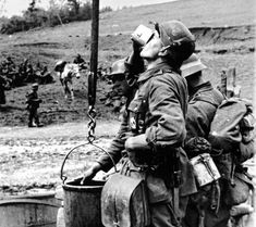 Wehrmacht soldiers drink water from a well in the Kharkov region.