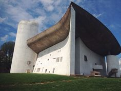 Kapel Notre-Dame-Du-Haut, Le Corbusier. Het kromme dak reikt naar de hemel. Doordat het niet wordt gedragen door de wanden maar door verstopte kolommen konden er subtiele glas stroken aangebracht worden tussen de wanden en het plafond. Dit zorgt voor een magisch lichtinval in de kerk van boven de wanden. Hierdoor lijkt het bovendien alsof het dak zweeft.