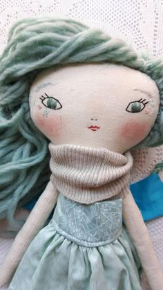 Joy doll - 17ish handmade cloth doll. this sweet joy doll has super thick and soft woolen hair that can be gently styled as you like. Her face and details are stitched by hand with love. She is wearing a scrappy woolen jumper under her minty dress. She has a crocheted cotton hood and little unicorn headband, a crocheted golden shawl and sweet felt boots. this line of dolls is my new favorite. They are substantial enough to hug, but darling enough for play. Their ears are stitched in to the…