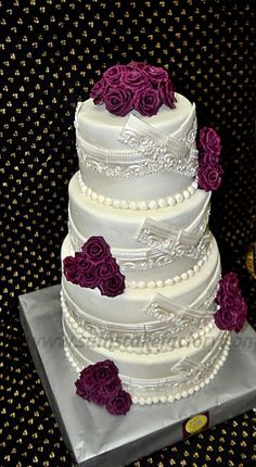 Four layer wedding cake. love the decorative design and purple flowers. :) <3