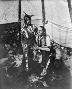 Siksika man with calumet and young boy inside tipi. 1914. Charlie Reevis, Crow Chief, with son.  South Piegan.
