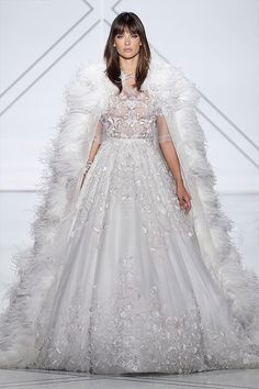 White tulle and pale grey organza layered bridal gown, adorned with crystals, glass bead hand embroidery and appliquéd with petit metallic flowers. Accompanied with a silk organza cape adorned with ostrich feathers.