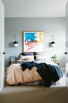bedroom of darren and dea from the block with bright abstract wall art on grey bedroom wall with wall sconces
