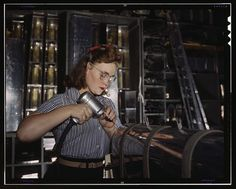Operating a hand drill at the North American Aviation, Inc., [a] woman is in the control surface department assembling a section of the leading edge for the horizontal stabilizer of a plane