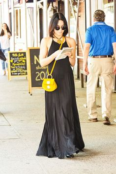 Vanessa Hudgens is wearing a black maxi, Thurloe sunglasses and goes for a pop of color in her yellow crossbody bag.