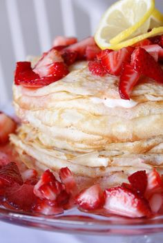 Lemon Strawberry Crepe Cake- Recipe Light golden crepes layered with sweet lemon cream cheese, topped with strawberries and fresh whipped cream.