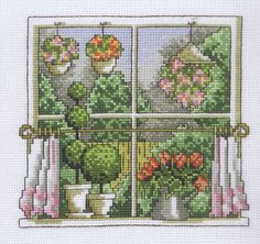 A window with a view on a bright green Spring garden with flowers inside and outside and pretty curtains.