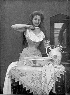 A woman brushing her teeth, photographed in 1899.