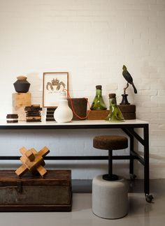 Among the Wiid Design pieces on the table are an etching by S Pratt and green lab vases by Ceramic Matters. The timber sculpture on the floor was inspired by Ethiopian jewellery.