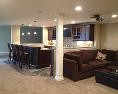 Great basement bar area: stacked stone, bar area, light blue accent wall and pendant lights