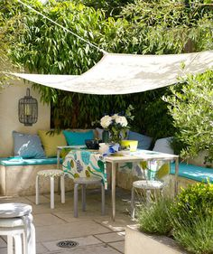 Patio Idea - If your outdoor space doesn't have an awning, create your own with a white fabric canopy. Have plenty of seating options (stackable stools, cushioned benches) so guests will feel welcome around the table.