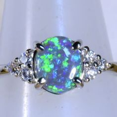 Solid 18k white gold Solid black opal & diamond dress/engagement ring. Dancing green, blue and violet coloring. Set with six brilliant cut HI colour VS clarity diamonds highlighting this fantastic N4 SOLID Lightning Ridge black opal 13763a