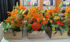Table centers of orange lilies, zinnia, asclepias, succulents, pieris japonica buds, Icelandic poppies and ranunculus by The Peony & The Peacock