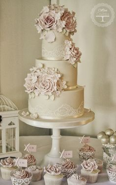 Beautiful cupcakes and wedding cake in elegant tones