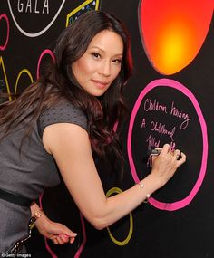 Making her mark: The actress penned a message onto a black wall during the gala