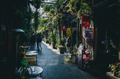 #alley #business #chairs #cobblestone street #commerce #daylight #group #market #outdoors #people #plants #road #shops #stores #street #tables #town #travel #trees #walking