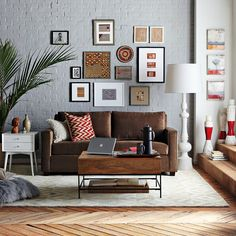 example of how to decorate around a dark sofa. The gallery style art, the pale gray walls, and the airy furniture accents combine to balance the visual weight of a dark sofa anchored in the center of the space Brown Couch Living Room, Living Room Grey, Home Living Room, Apartment Living, Living Room Decor, Apartment Interior, Brown Furniture, Brown Sofa Decor, Leather Furniture