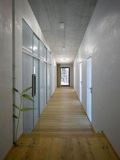 Exposed concrete ceiling, minimalist interior corridor house.