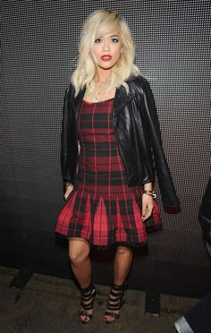 The Look: A pleated black and red plaid dress with a leather biker jacket worn on the shoulders.